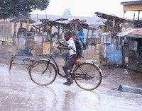 Oeganda - Kampala - jongen met fiets door de regen.